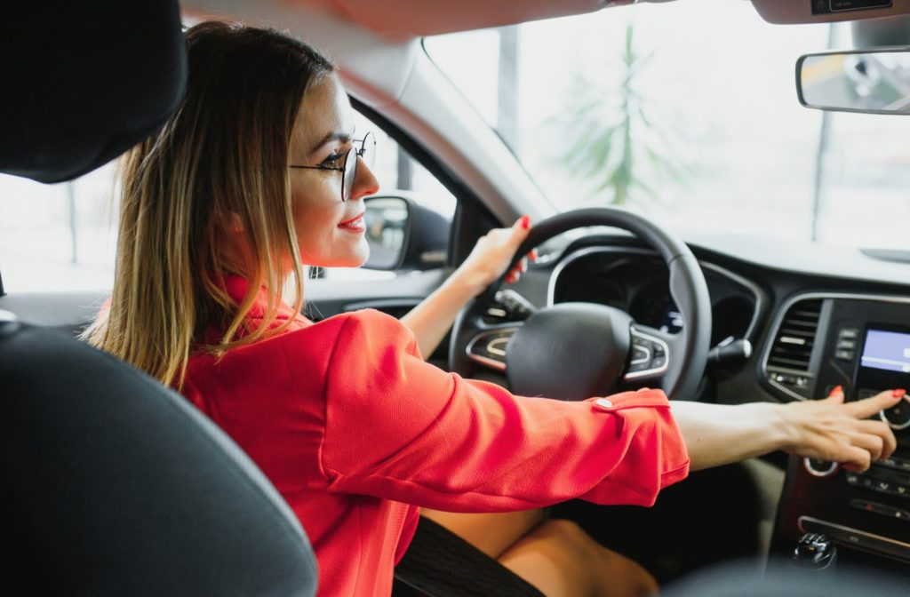 Young professional lady driving her car while wearing glasses